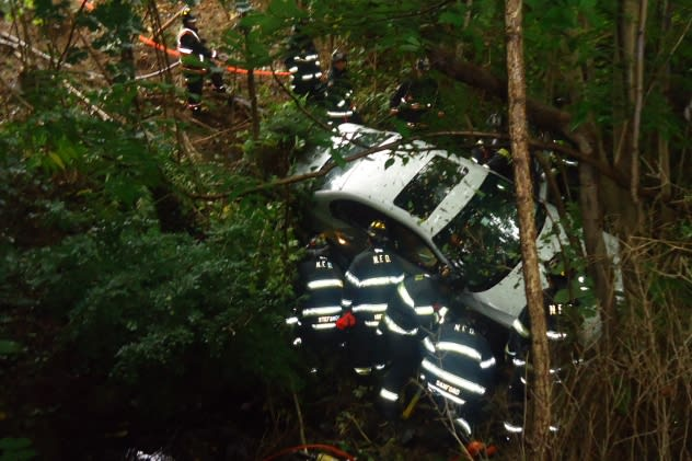 Norwalk firefighters work to stabilize a car that slid off the Merritt Parkway near exit 40 Tuesday morning.