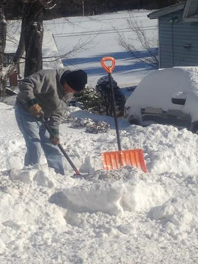 This man shoveling snow in Danbury is bundled up against the bitter cold.