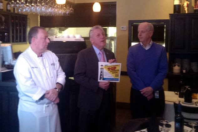From right: Norwalk Health Director Timothy Callahan and Mayor Harry Rilling give a Lighthouse Award to Mike's Pizza owner Nino Pagliarulo Tuesday.