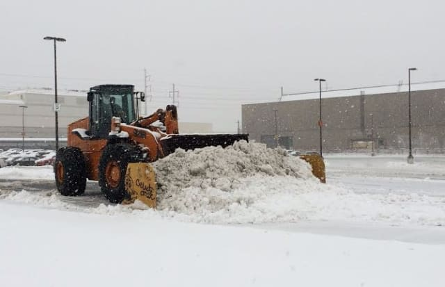 A front-end loader pushes the snow around Monday afternoon at the Fairfield Metro train station.
