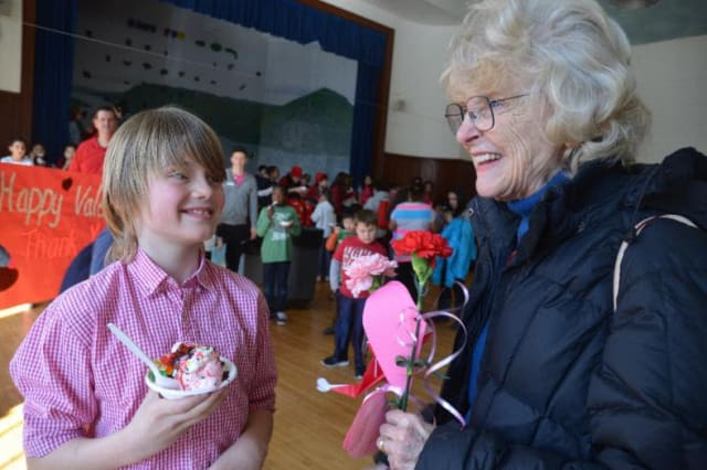 Rebecca Breed, right, shares a laugh with a boy at a previous Valentine's Day ice cream party at the Boys & Girls Club of Greenwich.