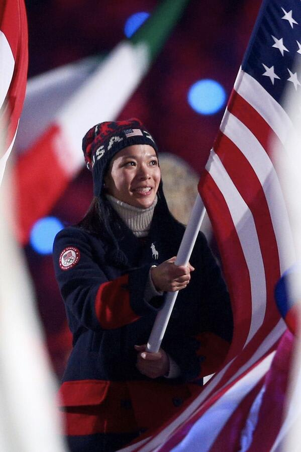Julie Chu carries the U.S. flag at the closing ceremony in Sochi on Sunday.