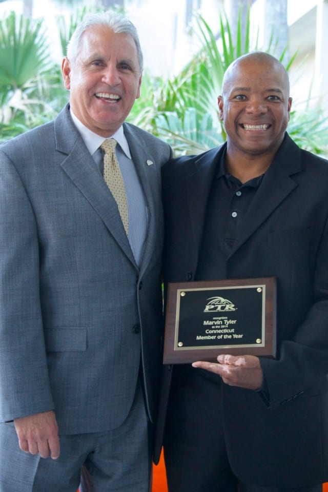 Norwalk's Marvin Tyler, right, receives the Professional Tennis Registry's member of the year award for Connecticut from  PTR board president Jorge Andrew.