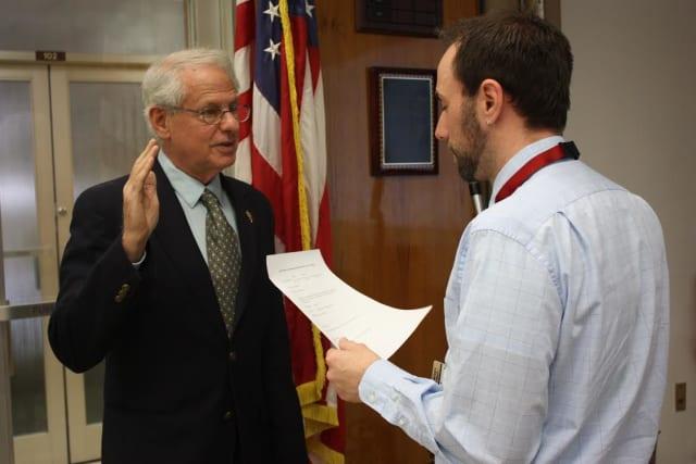 New Mount Vernon School Board President Leonard Sarver being sworn in by district Clerk Richard McCormack.