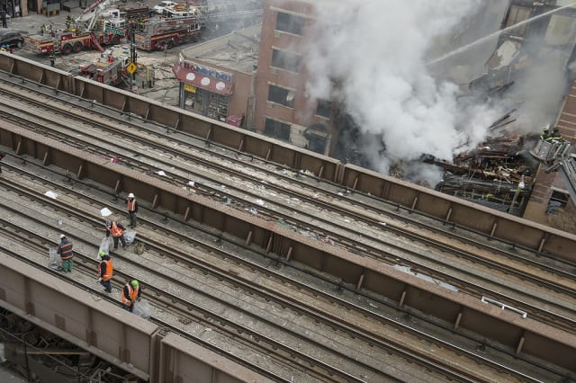 Crews clear debris on Metro-North tracks adjacent to scene of a building collapse at 116th Street and Park Avenue in East Harlem.