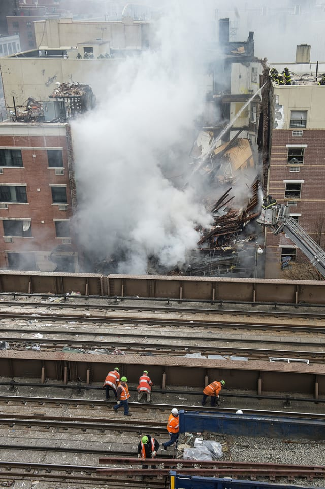 Crews clear debris on Metro-North tracks adjacent to scene of a building collapse at 116th St. and Park Ave. in East Harlem. Service was restored on all of Metro-North by late afternoon.