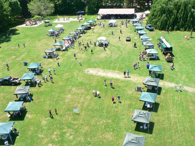 A panoramic view of the lineup of tree festival booths at Cranbury Park, as seen from a cherry picker.