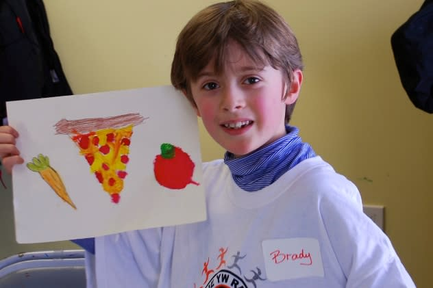 Brady Sullivan proudly holds up his painting created at the February Painting Workshop at the YWCA Darien/Norwalk.