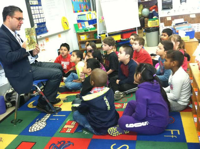 Vinnie Fusco, GM and executive in Charge of Production at NBCUniversal's Stamford Media Center, reads to Grade 1 students at Toquam Magnet School on Tuesday.