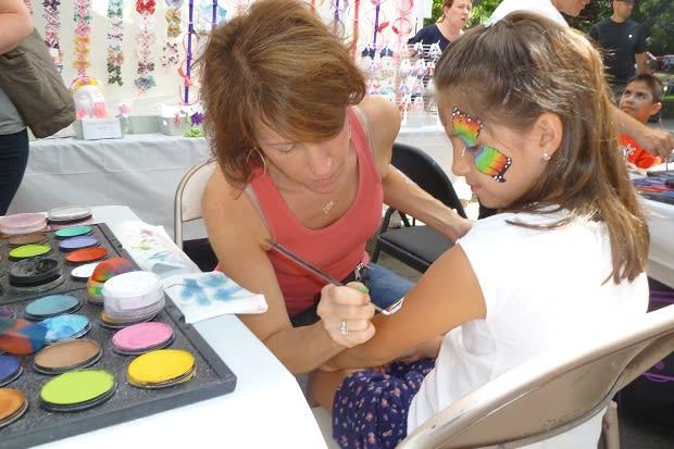 A girl gets her arm painted with an Italian flag Sunday at the 2012 Pelham Street Fair.