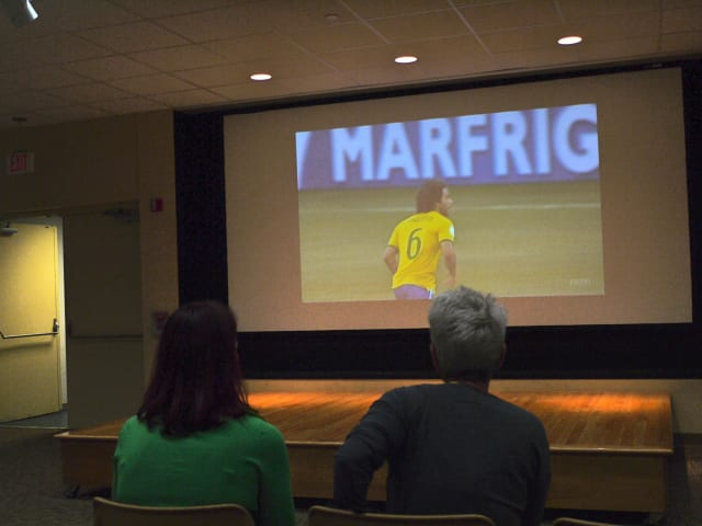 Westport residents Barbara Powell and Patricia Bello watch the first match of the World Cup tournament, cheering on Brazil in the McManus Room at the Westport library.
