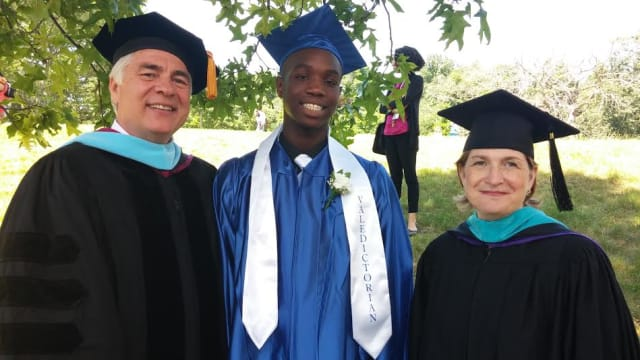 Orchard School Principal  Raymond Effinger and President and CEO Mimi Clarke Corcoran flank Tarik, one of two valedictorians of the Class of 2014.