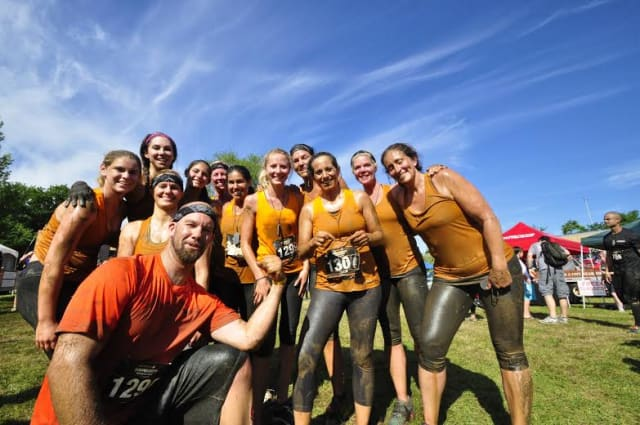 "Team Sherpa from Westport celebrates after completing the ""Down & Dirty"" obstacle race in Hartford."