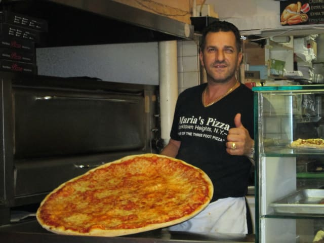 Sam Sahini in front of one of Maria's famous 3-foot pies.