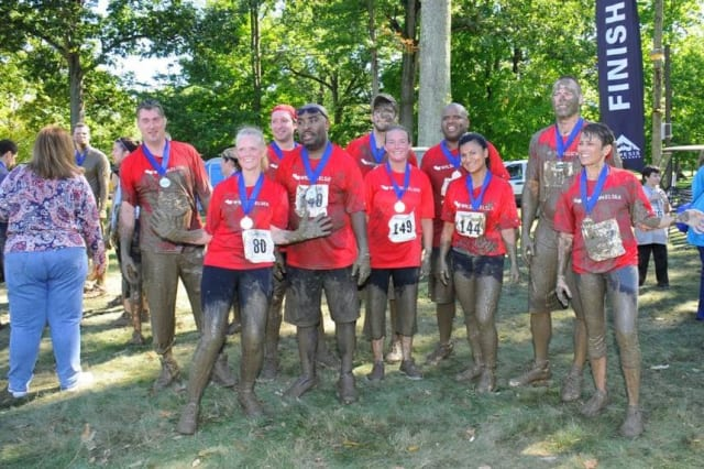 Muddy runners from Team Wilson Elsner gathered for a group photo after last year's Trauma Mud Run at Westchester Medical Center.