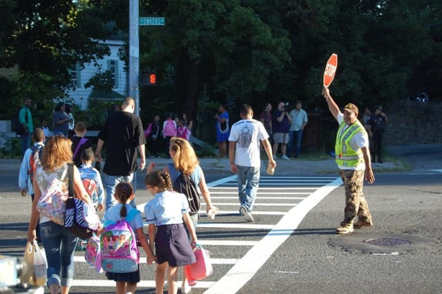 Children walk across the street as a Yonkers crossing guard watches the traffic.