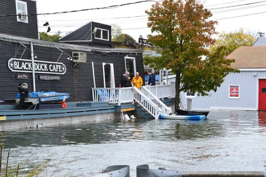 Flood waters reach the Black Duck Cafe on Riverside Avenue Monday following one of three expected high tide cycles.