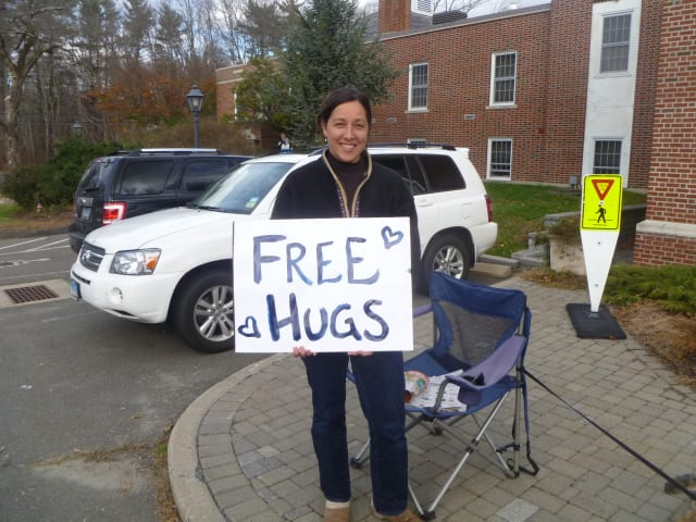 Kiko Teed offered free hugs to passersby near the Easton police station Thursday as residents picked up food and water.