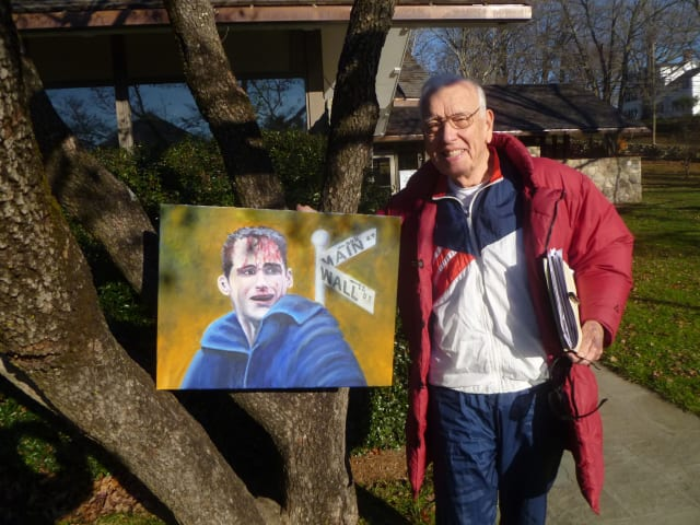 Keith Brooks, who is launching Occupy Weston, poses with a picture he painted that relates to the financial crisis.