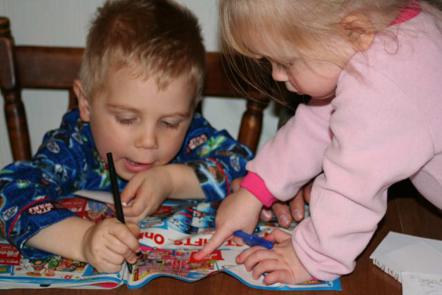 Maddy, right, helps her brother, Colin, select toys from a catalog to help him create his wish list for the Friends of Karen's Adopt-a-Family program.