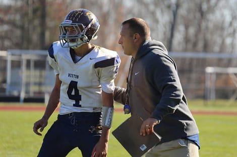 Weston coach Joe Lato, right, confers with quarterback Tyler Hassett during the win over Joel Barlow.