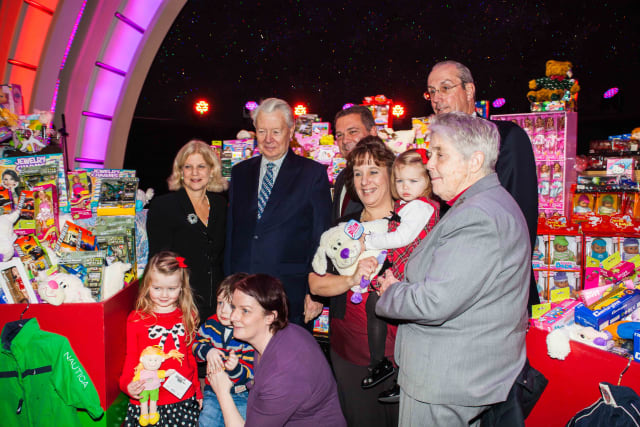 Empire City Casino CEO Timothy Rooney (center) joined city and county officials in presenting hundreds of donated toys Monday to Catholic Charities inside Empire City Casino.