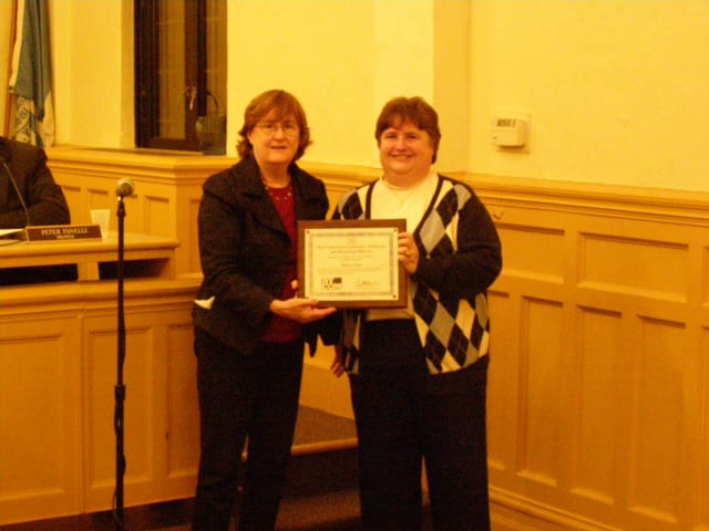 Mayor Anne H. McAndrews presents Eileen Finn, village clerk, with the NYCOM Service Award