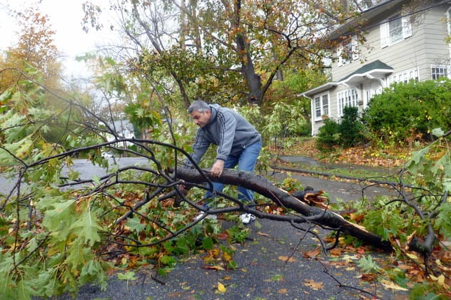 Aijaz Ahmed drags broken tree limbs from the road in front of his Yonkers home on Hillcrest Avenue in the aftermath of Hurricane Sandy.