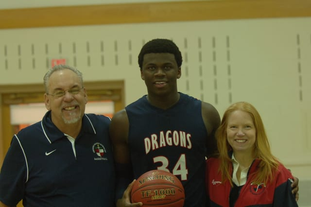 Greens Farms Academy basketball player Sean Obi, center, stands with his host parents from Greenwich, Steve and Bobbi Eggers after surpassing 1,000 career points.