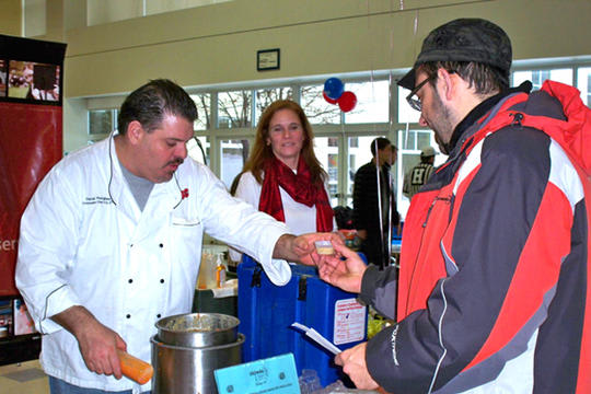 A participant at a past year's Chowdafest receives a chowder sample from Southport Brewing Co.