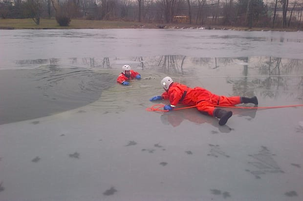Two members of the Greenburgh Technical Rescue Team practice a mock rescue at the Elmwood Country Club's lake.
