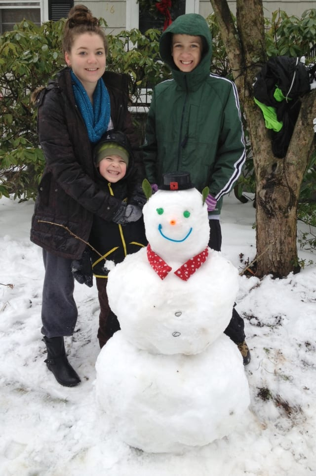 Taylor Copeland-York, left,  17, Luke Camarlinghi, 13, and Ethan Goormastic, 6, of New Canaan made a snowman Wednesday on their snowy day off from school.