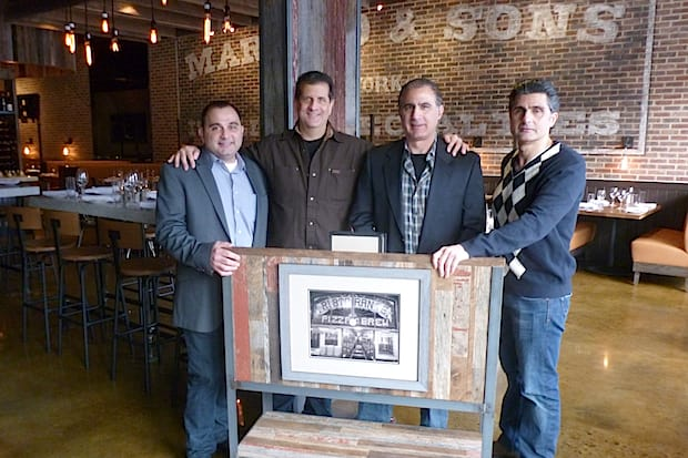 From left, Martin Racanelli, Nick Mautone, Alex Racanelli and John Racanelli stand behind a picture of the original Racanelli's Pizza and Brew. The newly-renovated Greenburgh restaurant re-opened in December.