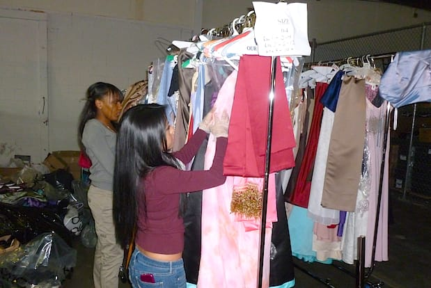 At the Westchester County warehouse Friday in Elmsford, members of Operation Prom organize dresses left over from last year.