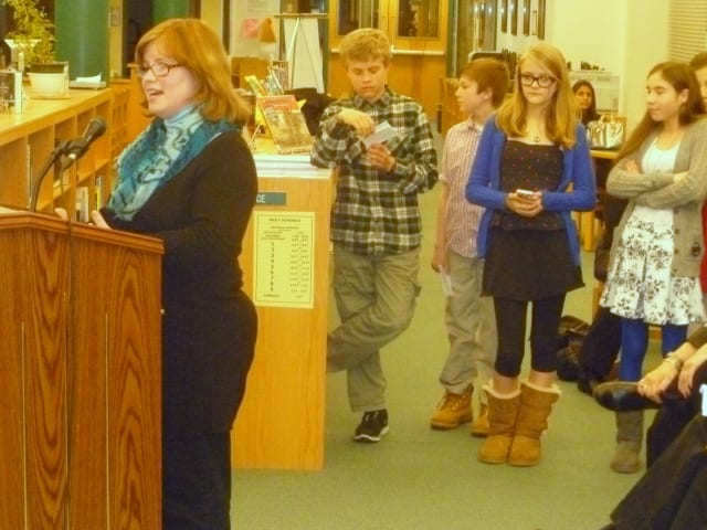 John Jay Middle School teacher Laura Atwell explains the 26-Day Challenge to the Board of Education as some of the students who participated look on.