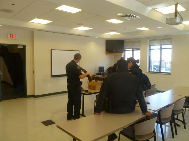 Police officers examine the shotgun turned in by Dan Hoffkins of Norwalk.
