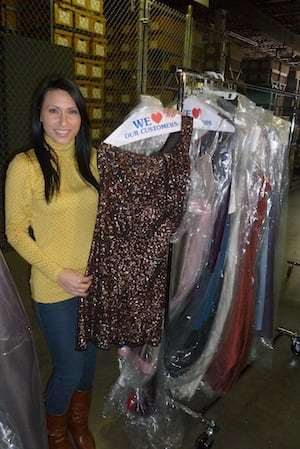 Noel D'Allacco, founder of Operation PROM, holds up a dress at the organization's storage facility in Elmsford. Operation PROM is raising money for a Queens high school prom.