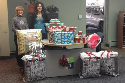 Gail Fattizzi, left, Executive Director of Westchester Real Estate, Inc., and Debra Budetti, member of Westchester Real Estate, Inc., show holiday gifts purchased for The Bridge Fund family.