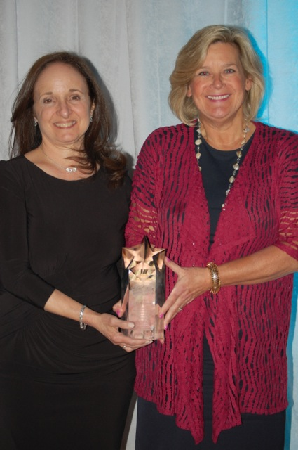 Diane Rosenthal, executive director of NFTE Fairchester, gives Ellen Lynch, executive director of Food Bank for Westchester, the award for Exemplary Volunteer Service .