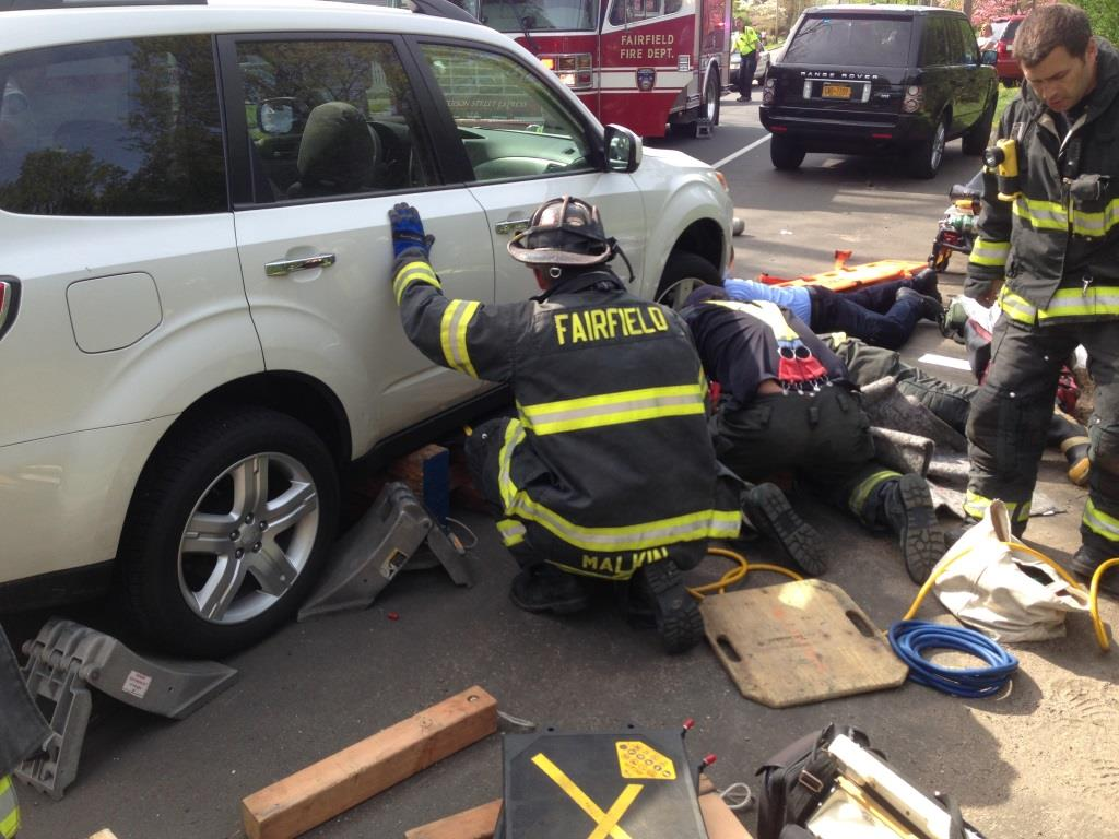 Fairfield and Bridgeport firefighters worked to raise a vehicle to pull an injured woman out from under the car.