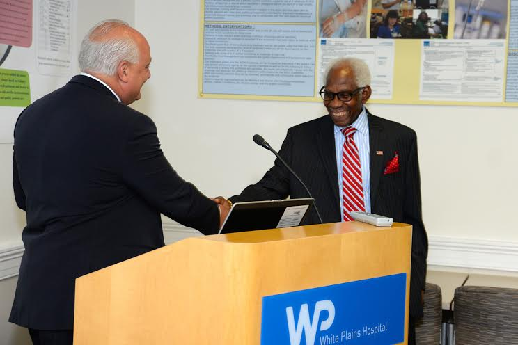 Dr. Valiere Alcena, longtime member of the White Plains Hospital medical Staff, shakes hands last week with the hospital's Executive Vice President and Medical Director Dr. Michael Palumbo at reception.