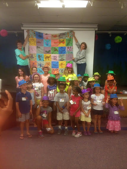 Vacation Bible School participants proudly display their quilt.