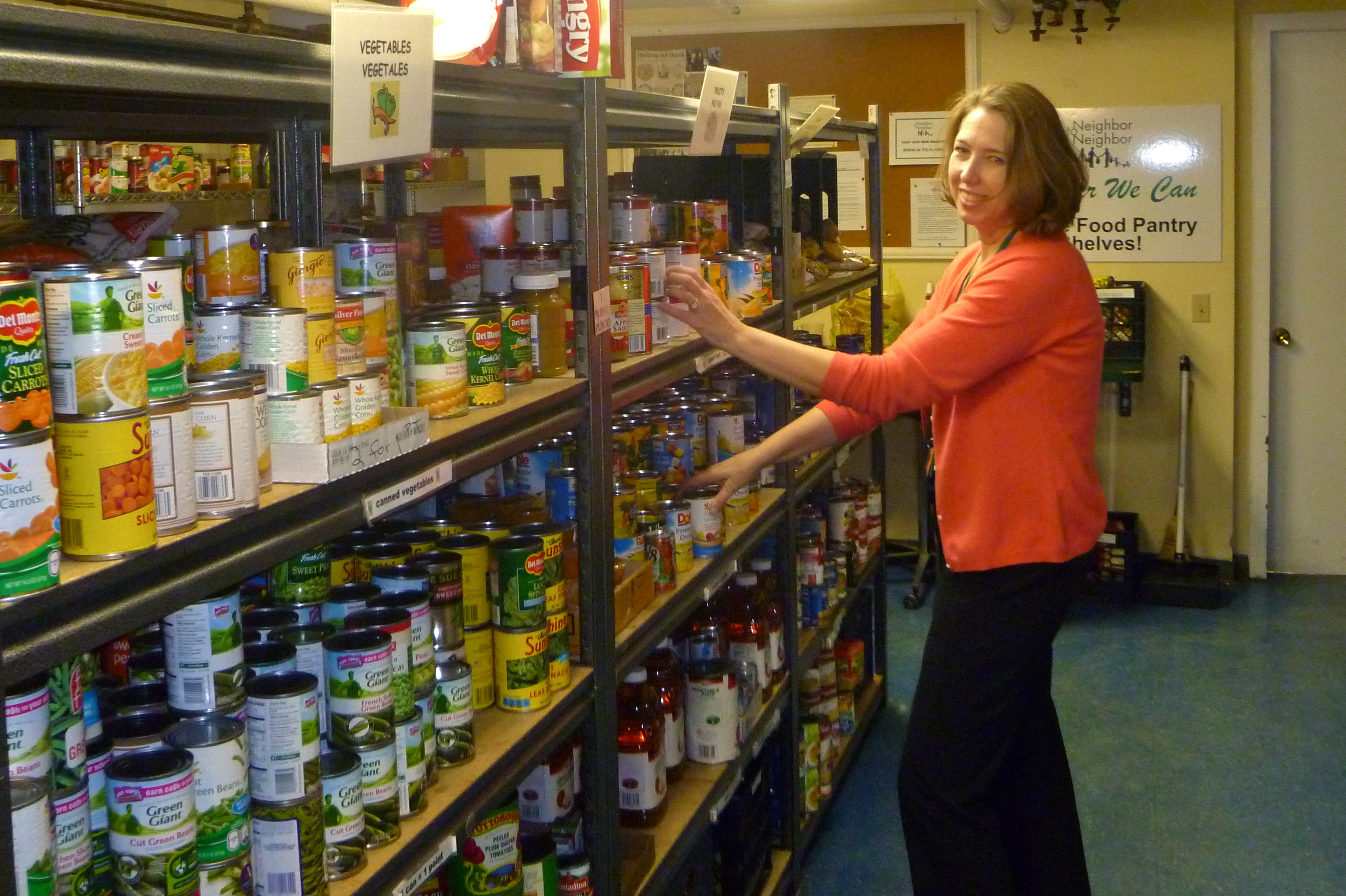 Nancy Coughlin, executive director of Neighbor to Neighbor, stocks the shelves of the organization's food pantry in the basement of Christ Church Greenwich.