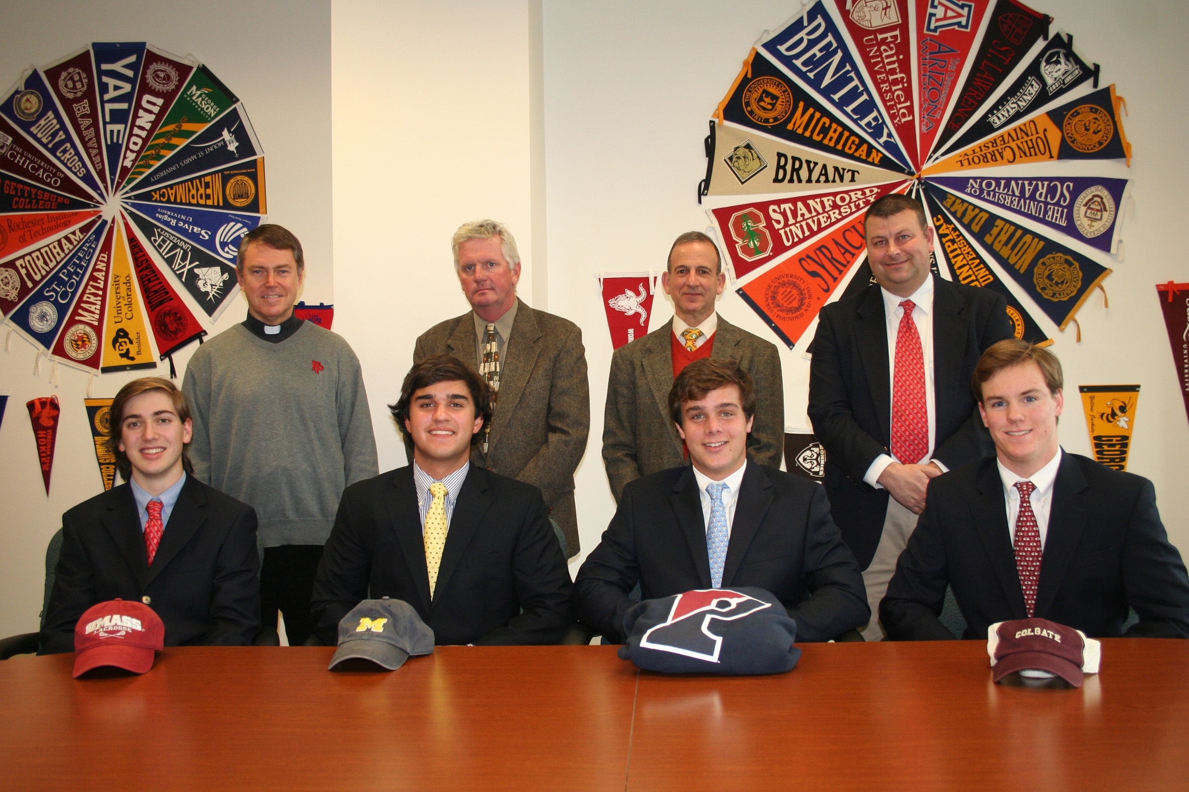 Fairfield Prep lacrosse players (front, left to right) James Marusi, Andrew Hatton, Kevin Brown and Strecker Backe recently made their college choices. They are show with (back, from left) Rev. John Hanwell, coach Chris Smalkais and AD Steve Donahue.