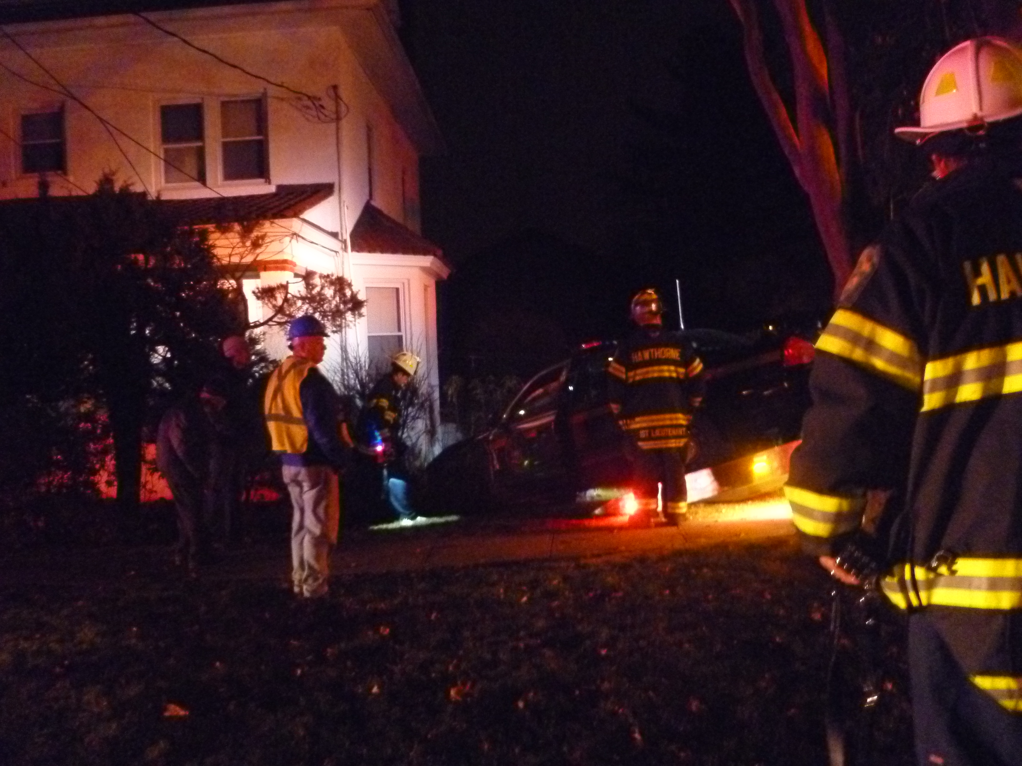 Firefighters watch a state police car being pulled from a house in Hawthorne on Saturday night.