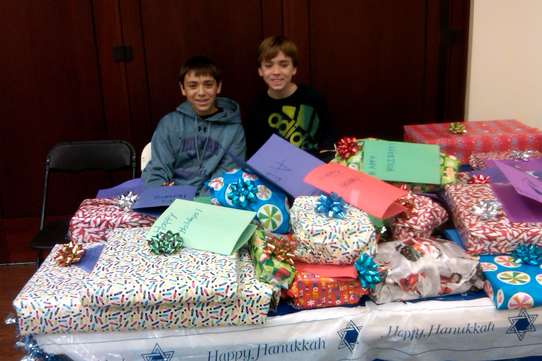 Chad, left, and Jonah Schwam pose with wrapped presents for children at the Pleasantville Cottage School.