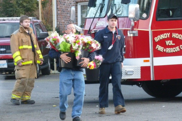 A man carries flowers at the Newtown firehouse next to Sandy Hook School in Newtown.