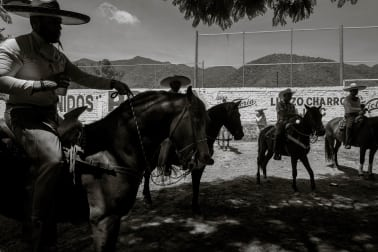 Cowboys on their horses drink and talk before the day