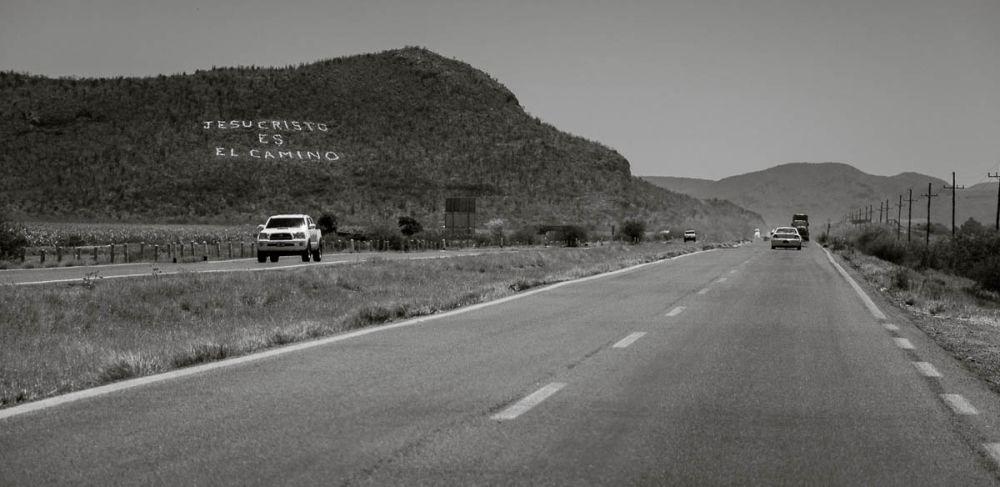 """""""Jesus Christ is the Way"""" is written on a hillside beside Highway 15 in Sinaloa, Mexico."""