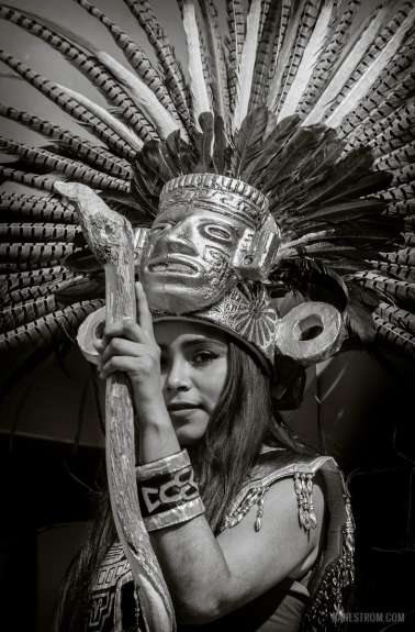 A young woman as an Aztec goddess stands on a moving float during the 2015 New Year's Day parade in Ajijic, Jalisco, Mexico
